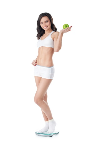 Yound fit girl holding apple standing on scales photo