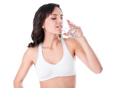 美しいブルネット スパ女性の頭の上にタオルで水を飲む