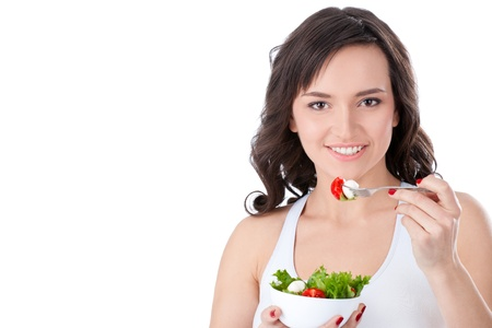 Young girl eating salad sitting on her bed at home Stock Photo - 11766259