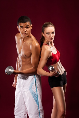 strong young man and woman working out with dumbbells Stock Photo - 11432234
