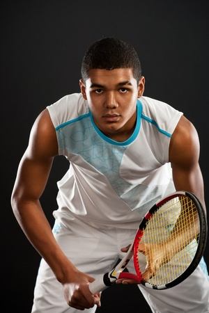 Young tennis player with racket ready to catch a tennis ball Stock Photo
