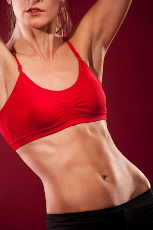 Body of a young fit woman lifting dumbell. Shot in studio on a red background. photo
