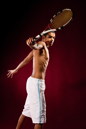 male tennis players: Young tennis player with racket hitting a tennis ball