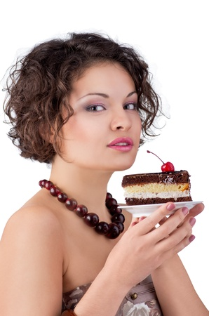woman eating cake: Attractive brunette woman with a cake looking in camera