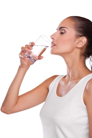 Beautiful brunette spa woman drinking water in towel on head Stock Photo