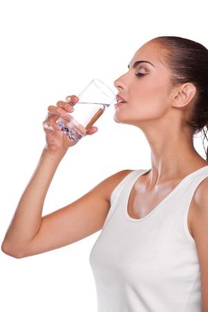 drinking glass: Beautiful brunette spa woman drinking water in towel on head Stock Photo