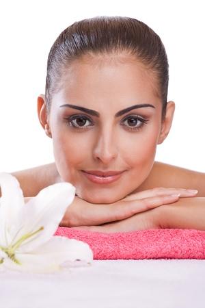 Beautiful brunette spa woman lying on towel in spa salon photo