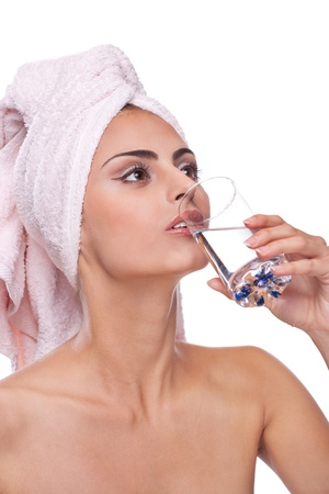 Beautiful brunette spa woman drinking water in towel on head photo