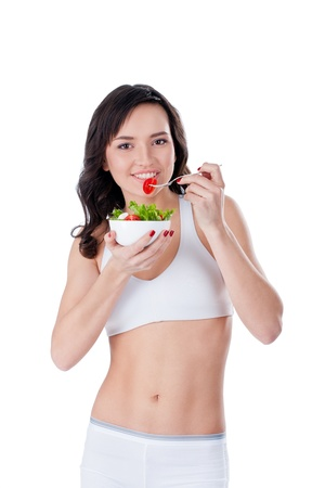 Young sportive girl eating green salad; isolated on white Stock Photo - 11853839