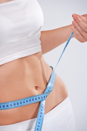Woman measuring waist of perfect body. weight loss concept photo