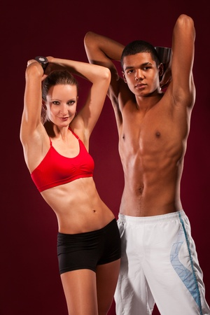 strong young man and woman working out with dumbbells photo