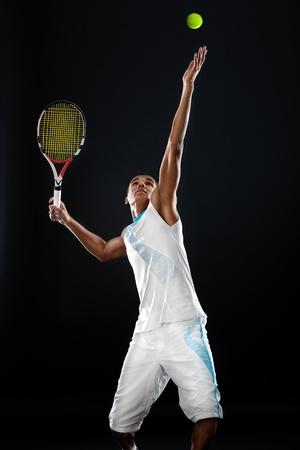 raqueta de tenis: Joven jugador de tenis con la raqueta lista para servir una pelota de tenis