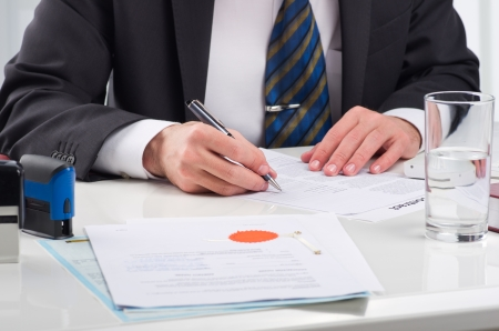 technology agreement: Notary public signing document at his workplace