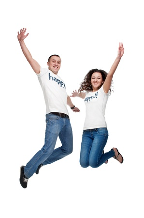 jeans girl: Young happy couple jumping up isolated on white