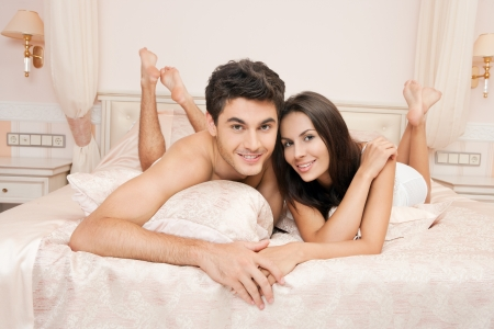 couple bed: Young adult heterosexual couple lying on bed in bedroom