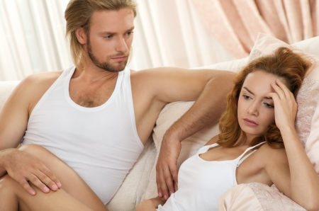 lying on bed: young upset couple lying in a bed having problem