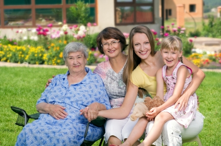 grandmother grandchild: Four generations of women sitting together at countryside and smiling Stock Photo