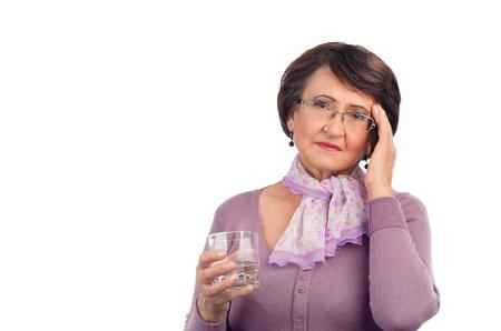 水のガラスを保持している頭痛と年配の女性