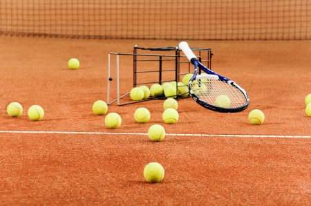 red clay: Tennis balls scattered from basket on court
