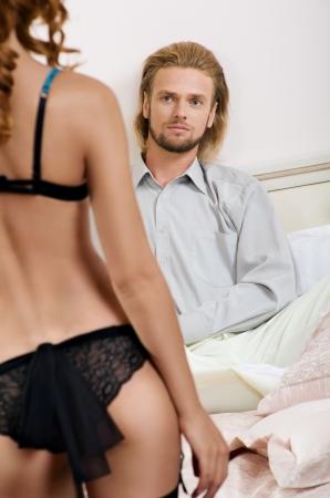 mujer sexy en ropa interior de pie delante de un hombre en la cama photo