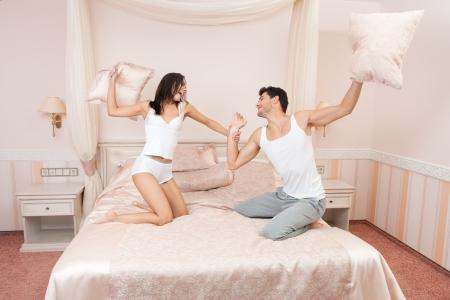 Casal jovem travesseiros de combate no quarto Imagens