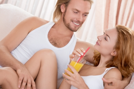 sleepwear: Beautiful couple at morning lying in bedroom