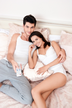 Happy couple lying down in bedroom watching television together Stock Photo - 15681318