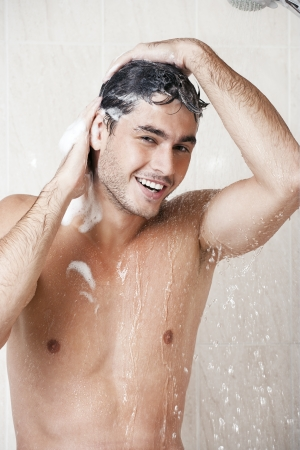 Young cute man washing head in bathroom Stock Photo