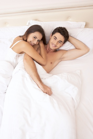 couple in bed: Young adult heterosexual couple lying on bed in bedroom