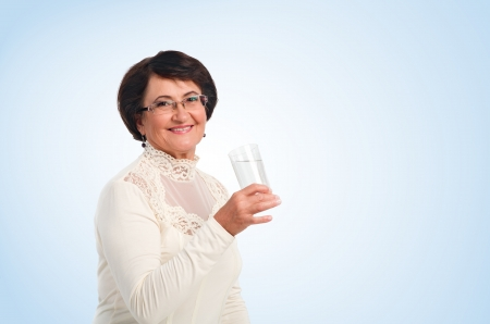 Portrait of elderly woman with glass of water  smiling in camera Stock Photo - 15896983