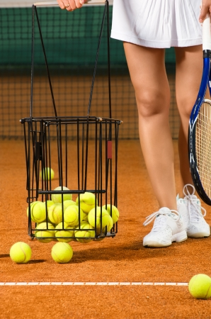 tennis skirt: Woman player gathering into basket tennis balls