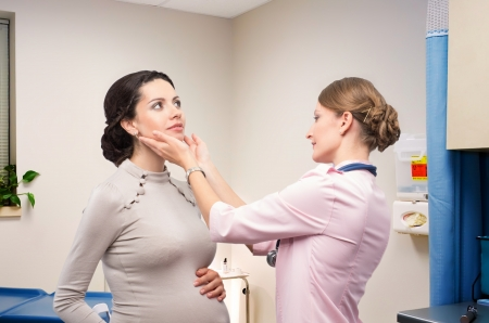 pregnancy: Doctor endocrinologist checking thyroid pregnant Stock Photo