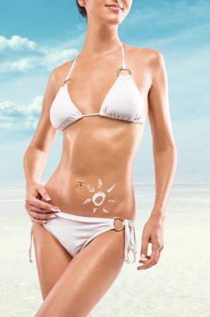 海のビーチでポーズのサングラスをかけた若いセクシーな女性