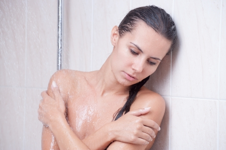disappointed and unhappy brunette girl in the shower photo