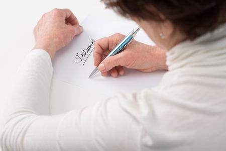 遺言を書く高齢者婦人の手
