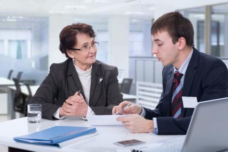 マネージャーは、オフィスで高齢者の女性に助言します。