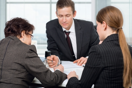 businessman signing documents: Agent  or notary public  signing documents with couple women