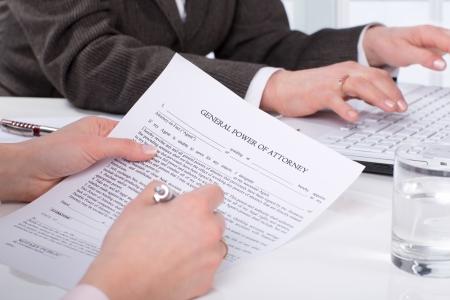 abogado: Manos de la firma del documento mujer sentada en el escritorio Foto de archivo