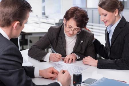 legal document: mujer mayor firma de un documento en la oficina con los administradores Foto de archivo