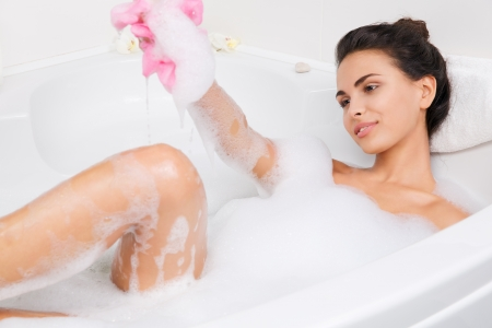steam bath: young beautiful brunette woman takes bubble bath