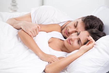 Young adult heterosexual couple lying on bed in bedroom Stock Photo - 18731422