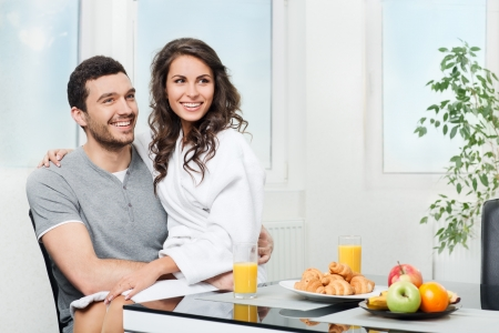 beautiful couple having breakfast table, girl sits on hands for a boyfriend photo