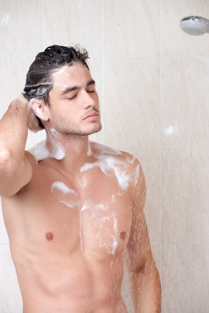 Young cute man washing head in bathroom Stock Photo