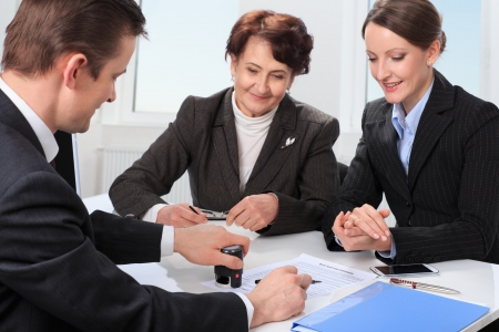 Agent  or notary public  signing documents with with senior woman and her daughter