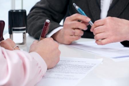 legal document: Manos de la firma del documento mujer sentada en el escritorio Foto de archivo