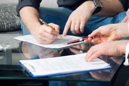 RÄ™ce dwóch mężczyzn podpisaÅ' dokument, siedzÄ…c przy biurku Zdjęcie Seryjne
