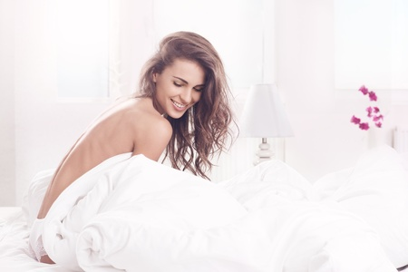 young beautiful girl woke up and sitting on a bed Stock Photo - 18971021
