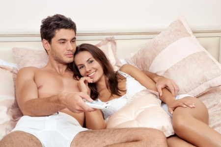 Happy couple lying down in bedroom watching television together Stock Photo - 19024924