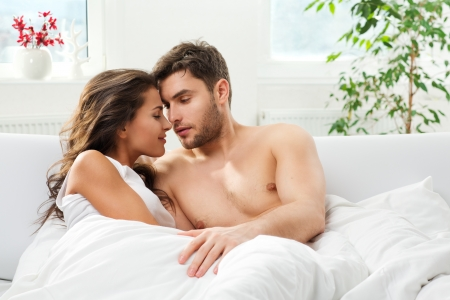 wife: Young adult heterosexual couple lying on bed in bedroom