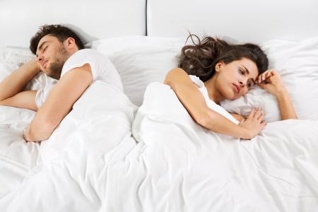 Jovem casal ter virado desacordo deitados lado a lado na cama de frente em dire Imagens